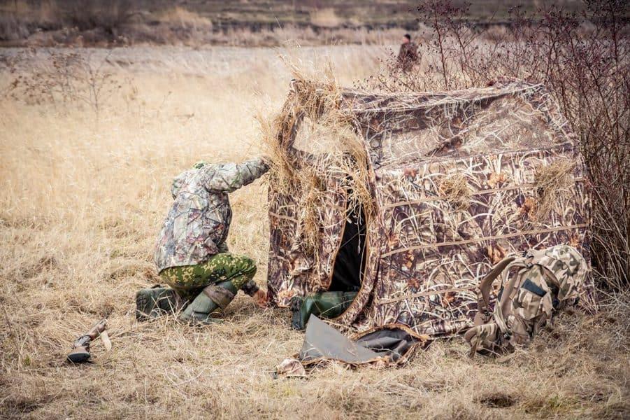 Man installing hunting tent in rural field