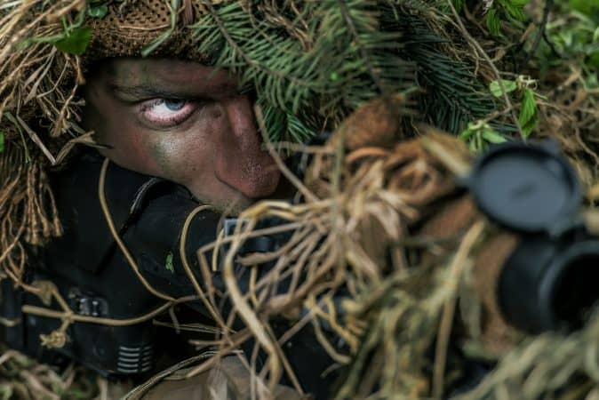 a camouflaged person aiming with a rifle