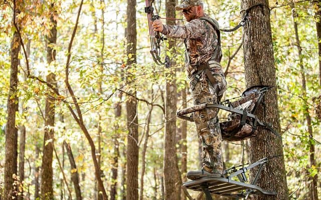 bowhunter on a climbing tree stand